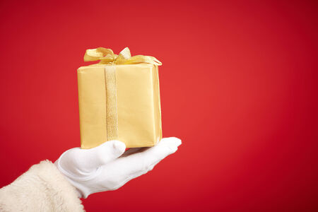 gloved: Santa Claus gloved hand with golden giftbox Stock Photo