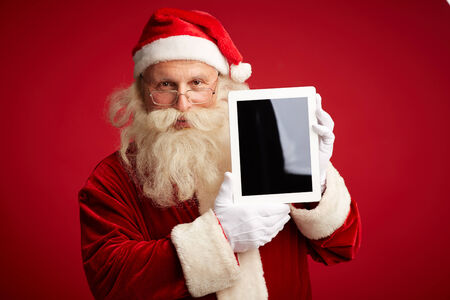 Portrait of Santa Claus with touchscreen looking at camera Stock Photo - 31125135