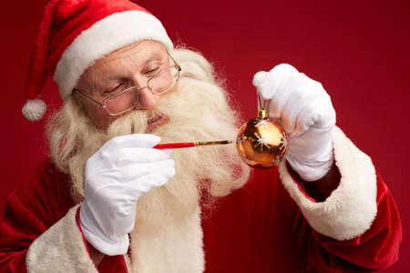 holding a christmas ornament: Portrait of Santa drawing snowflakes on decorative toy ball Stock Photo