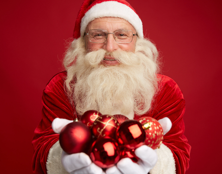 Portrait of Santa holding red decorative toy balls Stock Photo - 31125137
