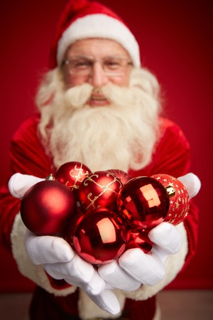 Santa holding red decorative toy balls on his palms Stock Photo - 31125138