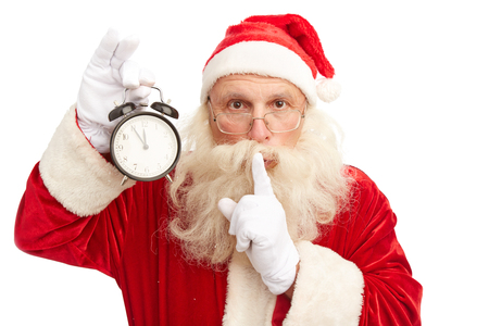 Santa Claus with alarm clock showing five minutes to midnight making shhh gesture and looking at camera Stock Photo - 31125142