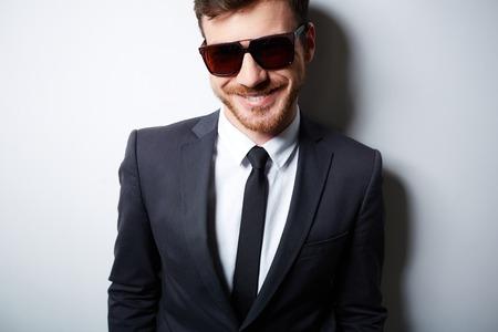 hombre con barba: Hombre de negocios fresco en traje y gafas de sol posando en el aislamiento Foto de archivo