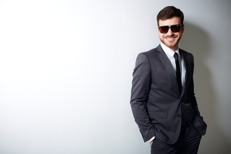 Happy young man in suit and sunglasses posing for camera