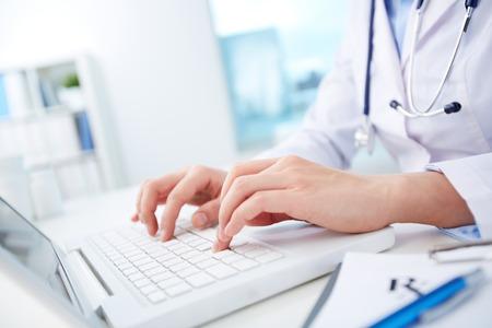ノート パソコンに入力する看護師の手のクローズ アップ