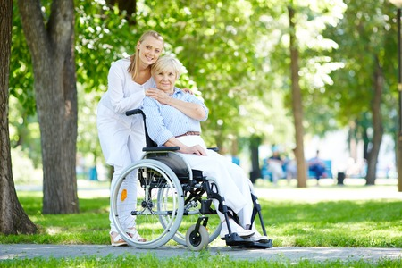 cares: Pretty nurse taking care of senior patient in a wheelchair