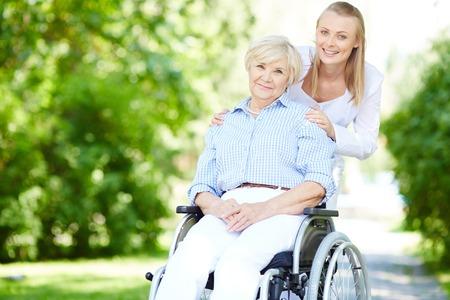 Vrouwelijke zorgverlener en senior patiënt in een rolstoel te kijken naar de camera buiten