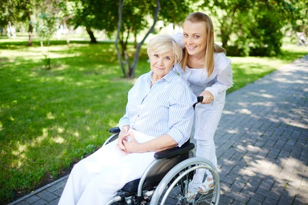 Female caregiver walking with senior patient in park photo