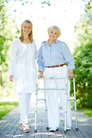 Pretty carer and senior patient walking outside photo