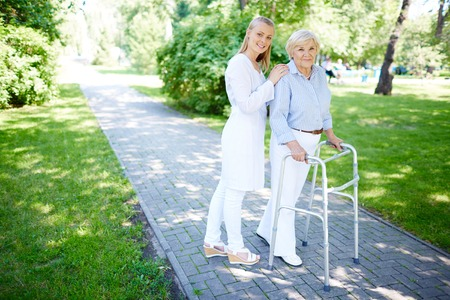 Pretty carer walking out with senior patient photo