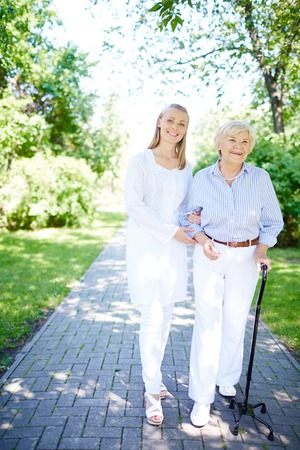 Pretty nurse and senior patient walking out in summer photo