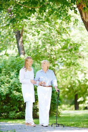 smiling people: Young caregiver and her senior patient walking out in summer park
