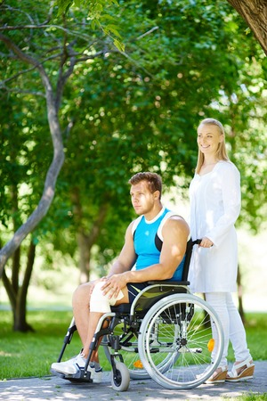 Pretty nurse walking with male patient in a wheelchair photo