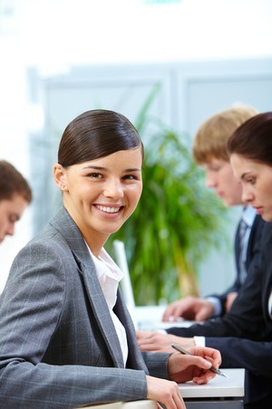 Portrait of smiling woman looking at camera on the background of working colleagues photo