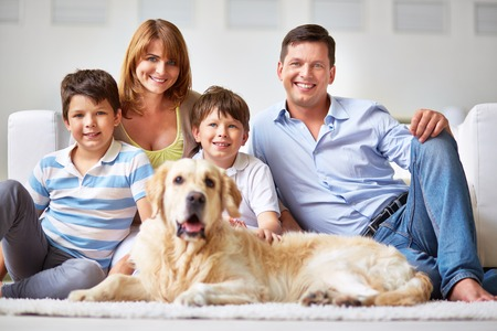 indoor inside: Happy family with two boys and a dog smiling at camera