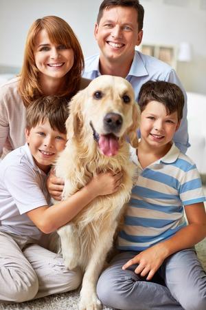Gezin van vier poseren met hun hond