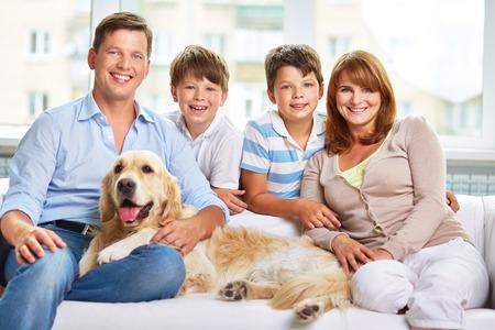 Familia feliz con un perro que se sienta en la sala de