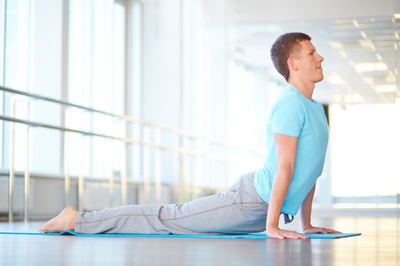 Healthy guy doing stretching exercise in gym photo