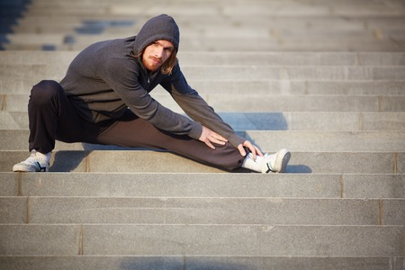 activewear: Portrait of young sportsman doing stretching exercise outside  Stock Photo
