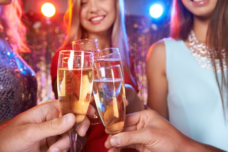 new year's: Hands of friends cheering up with champagne at party