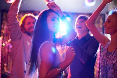 Joyful vrienden dansen in nachtclub