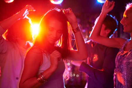 human energy: Pretty girls dancing in night club on background of guys