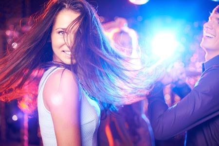 dancing club: Joyful brunette looking at camera while dancing in night club