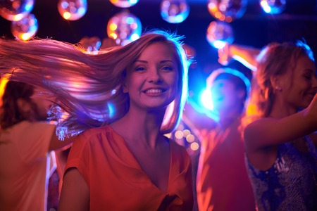 Joyful female looking at camera while dancing in night club with her friends on background