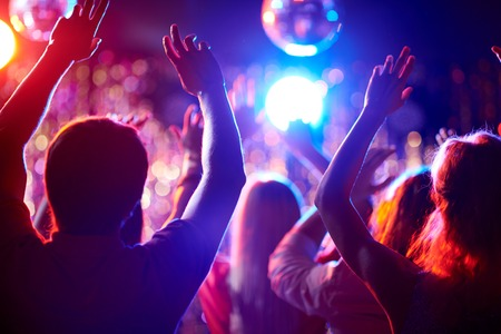 night club: Folla di persone con le braccia sollevate a ballare in discoteca