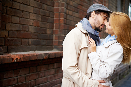 Portrait of amorous couple in stylish clothes outside