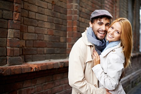 Portrait of affectionate couple in stylish clothes looking at camera outside photo