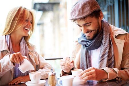 hombre tomando cafe: Retrato de pareja cariñosa en la ropa con estilo tomando un café en la cafetería