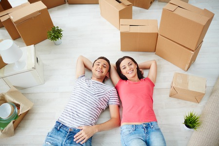 Happy young couple looking at camera while lying on the floor of new house photo