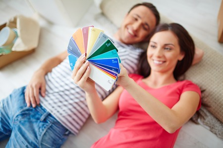 Happy young couple looking at colorful palette photo