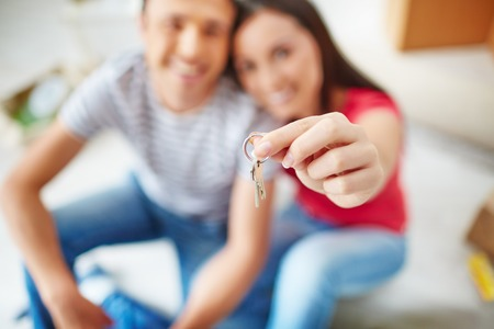 Hand of young woman holding key from new flat