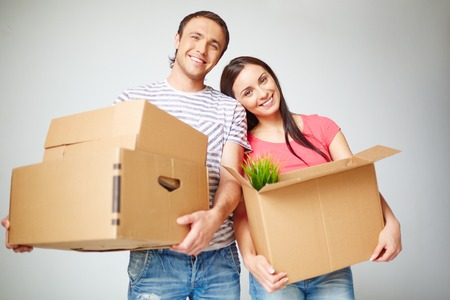 Happy couple with boxes in new flat