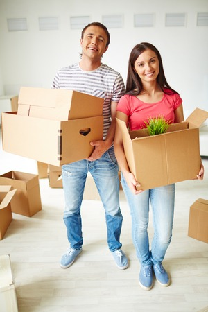 settler: Happy young couple with boxes standing on the floor of new flat Stock Photo