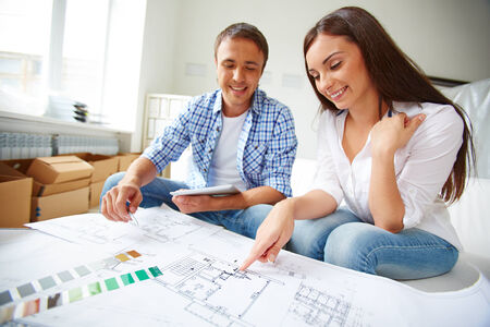 Portrait of young couple sitting in their new flat and discussing its plan Stock Photo