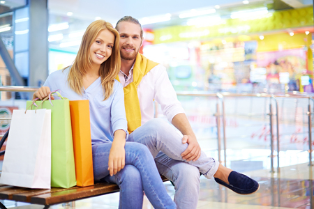 Young couple sitting on bench in shopping mall photo