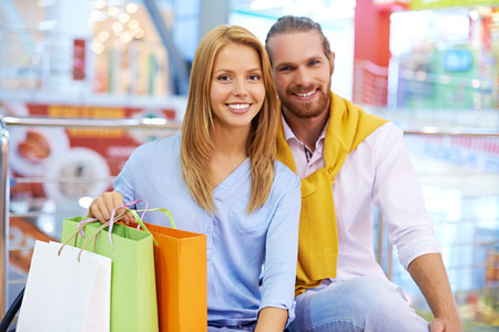 shopaholism: Portrait of a young couple with shopping bags