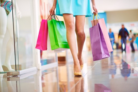 shoppers: Legs of shopaholic with shopping bags walking down mall