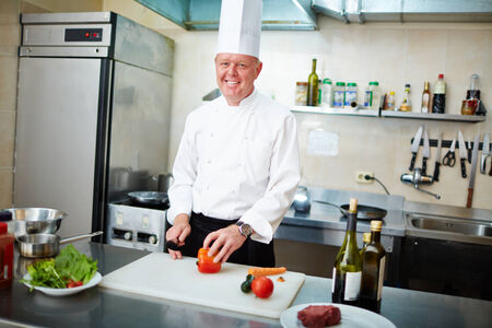 vegs: Image of male chef with knife and vegs preparing salad Stock Photo
