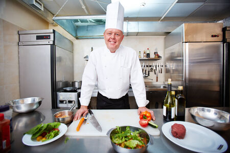Image of male chef looking at camera in the kitchen photo
