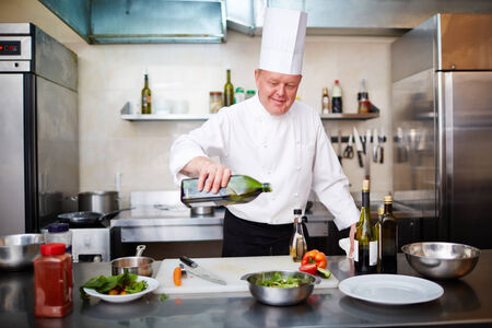 Image of male chef pouring olive oil into vegetable salad in the kitchen photo