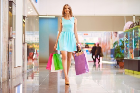 go inside: Pretty young shopper with shopping bags walking down mall