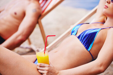 Woman with juice resting in deck chair with man on background   photo