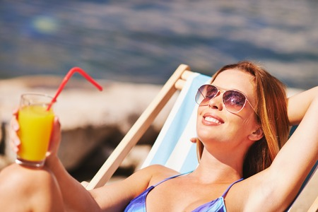 restful: Restful young woman with juice sunbathing on beach