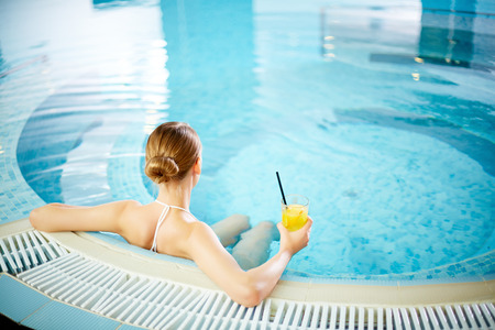 Young woman sitting in swimming pool with lemonade photo