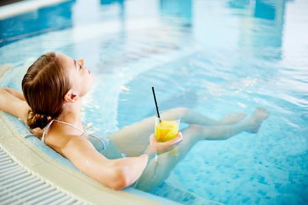nadar: Mujer que goza en la piscina después de los procedimientos Foto de archivo