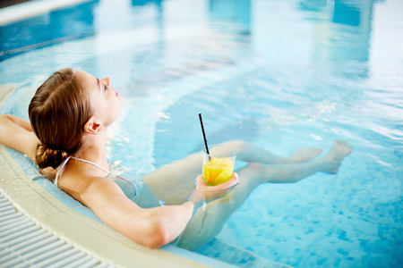Woman enjoying in swimming pool after procedures Stock Photo